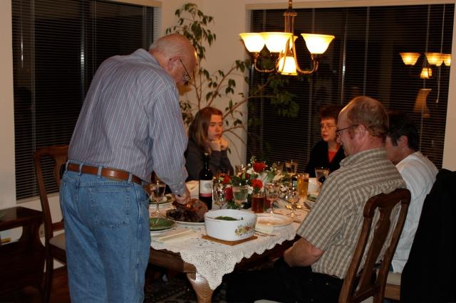 Al carving prime rib with Loki, Mom, Greg and Tom