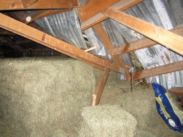 collapsed-roof-in-center-of-barn-in-hay-loft